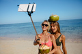Female friends taking picture with smartphone on selfie stick on - PhotoDune Item for Sale