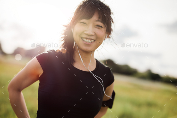Happy female running standing outdoors and smiling - Stock Photo - Images