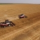 Two Red-white Modern Harvesters Working On a Field In Harvest Time,aerial Shot, Drone Flying Around - VideoHive Item for Sale