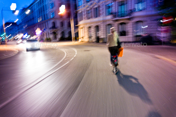 woman rides bicycle in the night - genuine motion blur and vibrant colors - Stock Photo - Images