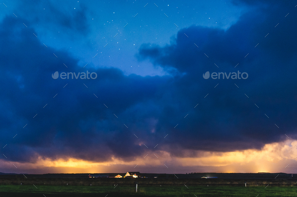 house under heavy clouds and northern lights - Stock Photo - Images
