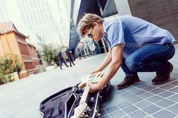 Young musician with guitar in city - Stock Photo - Images