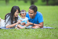 Happy family lying in the grass using smart phone