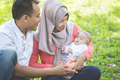 asian happy family with newborn baby in the park