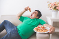 lazy overweight man eating pizza while laying on a couch - PhotoDune Item for Sale