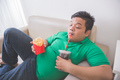 lazy obese person eats junk food while laying on a couch - PhotoDune Item for Sale