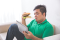 obese person eating hamburger while using tablet pc - PhotoDune Item for Sale