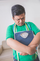 sad obese man holding a weight scale, thinking about his weight - PhotoDune Item for Sale