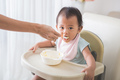 Happy Young Baby In High Chair being fed - PhotoDune Item for Sale