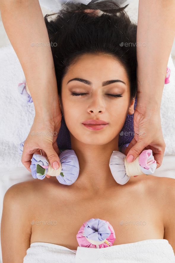 Woman has herbal ball massage in ayurveda spa wellness center - Stock Photo - Images
