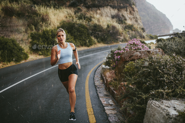 Fitness woman running on countryside highway - Stock Photo - Images