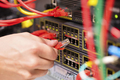 IT consultant connects a network cable into switch in datacenter - PhotoDune Item for Sale