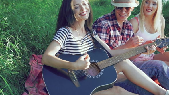 the girl plays guitar on the grass and friends clapping by maximumstock