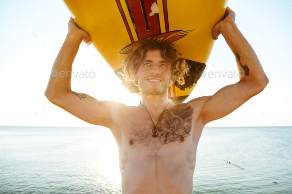 Close up face of handsome guy with surfboard on head - Stock Photo - Images