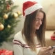 Pretty Girl In Christmas Cap Using Smartphone - VideoHive Item for Sale