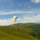 Paragliders Fly Near Amazing Green Mountain