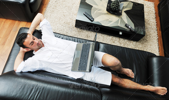 Portrait of a relaxed young guy using laptop at home - Stock Photo - Images