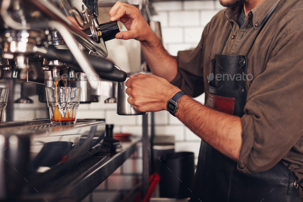 Barista making coffee using a coffee maker - Stock Photo - Images