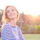 Happy Beautiful Young Woman Sitting on the Grass in City Park and Smiling at Sunset 3 - VideoHive Item for Sale