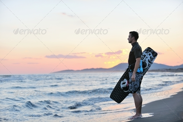 Portrait of a young  kitsurf  man at beach on sunset - Stock Photo - Images