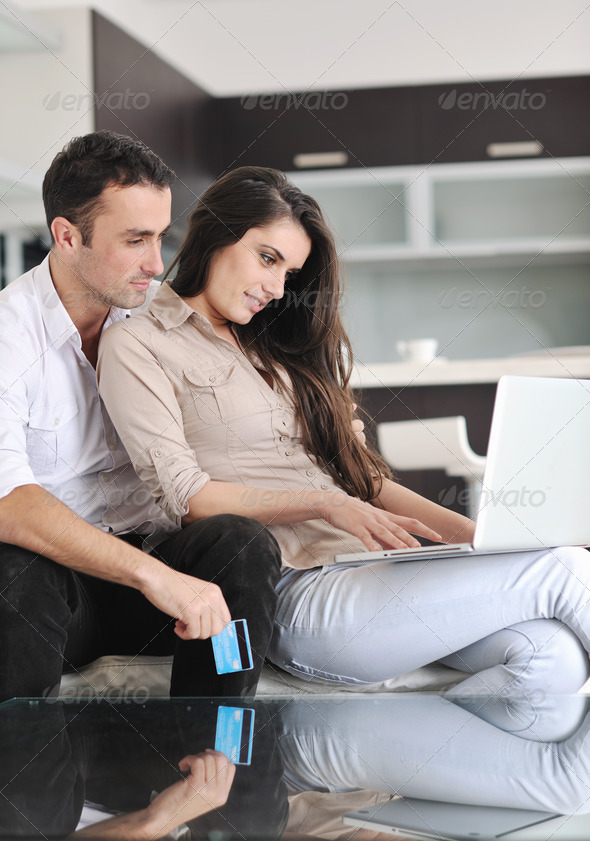 joyful couple relax and work on laptop computer at modern home - Stock Photo - Images