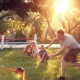 Parents Playing With Dog And Children At Home On Backyard - VideoHive Item for Sale
