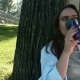 The Young Beautiful Girl Drinking Coffee In The Park - VideoHive Item for Sale
