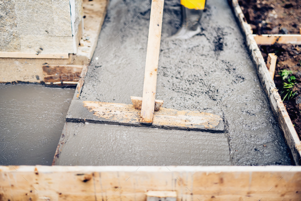 Mason building and leveling first layer of concrete floor  - Stock Photo - Images