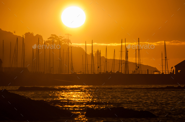 Silhouette of ships masts against sunset - Stock Photo - Images