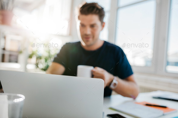 Laptop on table with man sitting by - Stock Photo - Images