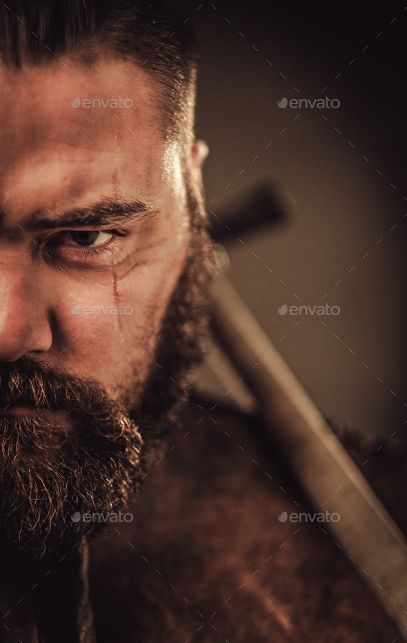 Angry viking with ax in a traditional warrior clothes, posing on a dark background. - Stock Photo - Images