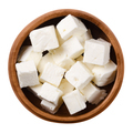 Greek Feta cheese cubes in wooden bowl over white