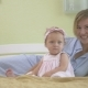 Baby Sitting Near The Mum On Bed - VideoHive Item for Sale