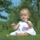 Little Girl Sitting On The Grass In The Garden. - VideoHive Item for Sale