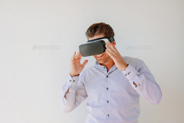 Happy businessman watches content on a virtual reality display - Stock Photo - Images