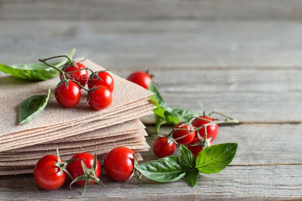 Raw lasagna sheets,basil and cherry tomatoes - Stock Photo - Images