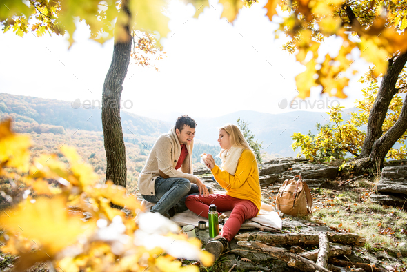 Beautiful couple in autumn forest eating and drinking - Stock Photo - Images