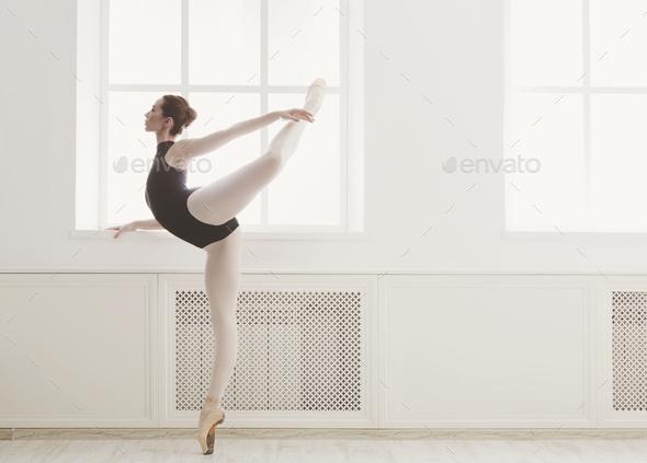 Beautiful ballerine stands in arabesque ballet position