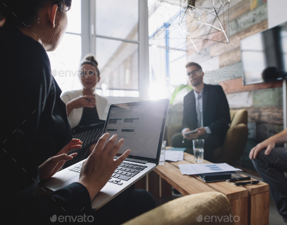 Businesswoman discussing business strategy with colleagues - Stock Photo - Images