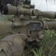 Sniper Lies Behind Cover In The Grass With a Gun In His Hand And Shoots - VideoHive Item for Sale