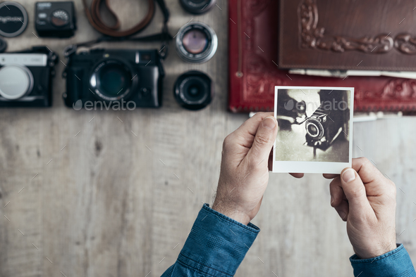 Photographer holding an instant picture - Stock Photo - Images