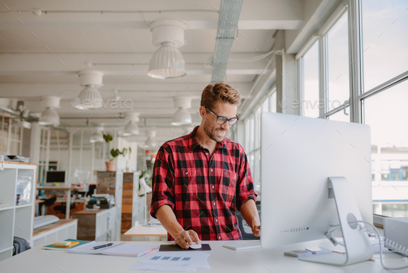 Young man working in modern workplace - Stock Photo - Images