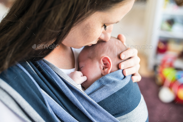 Unrecognizable young mother with her son in sling - Stock Photo - Images