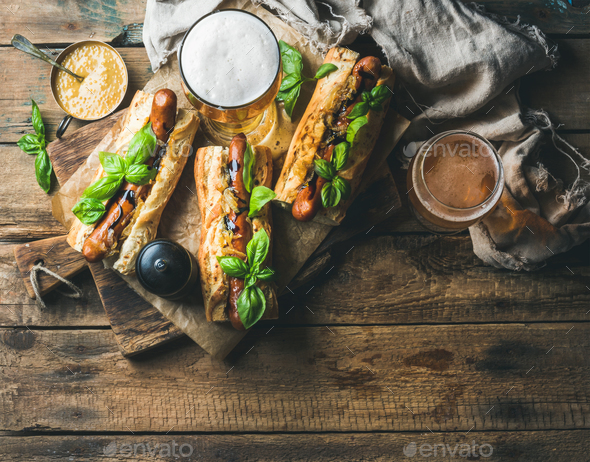 Glasses of wheat unfiltered beer and homemade grilled sausage dogs - Stock Photo - Images