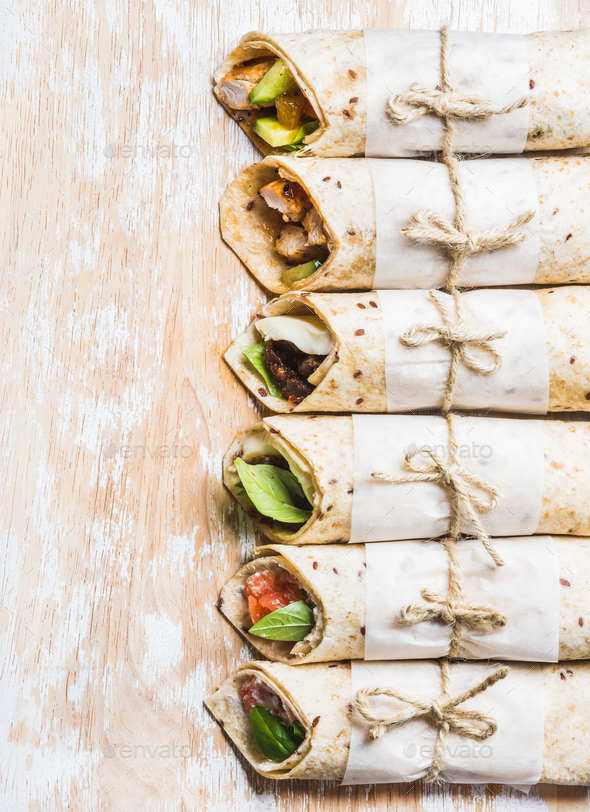 Tortilla wraps with various fillings on shabby white wooden board - Stock Photo - Images