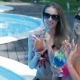 Two Women Drink Cocktails On The Swimming Poolside - VideoHive Item for Sale