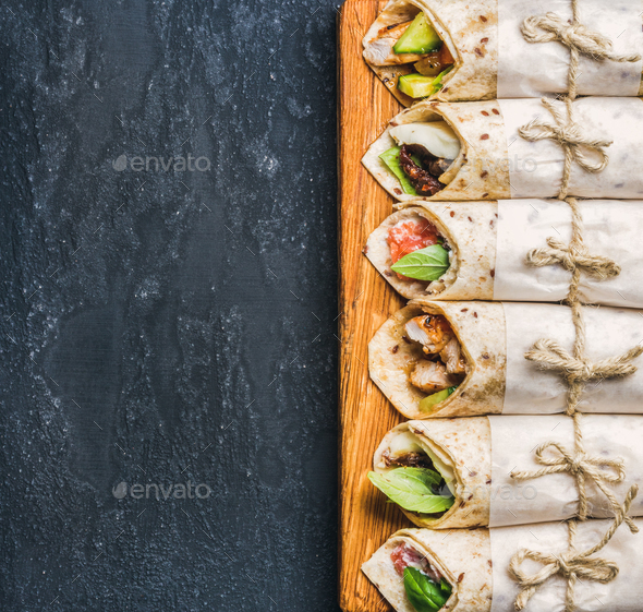 Tortilla wraps with various fillings on dark grey concrete background - Stock Photo - Images
