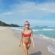 Beautiful Caucasian Christmas Woman In Santa Hat And Red Bikini Jokes And Relaxing On The Beach With Nulled