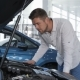 Man Looks at the Engine Compartment of the Car at the Dealership - VideoHive Item for Sale