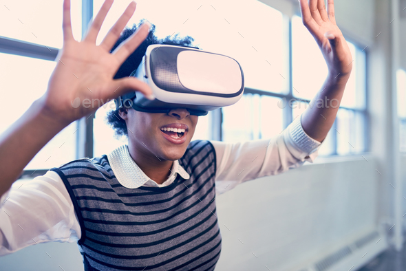 Cool millennial black woman exploring virtual reality glasses in an open-concept space - Stock Photo - Images